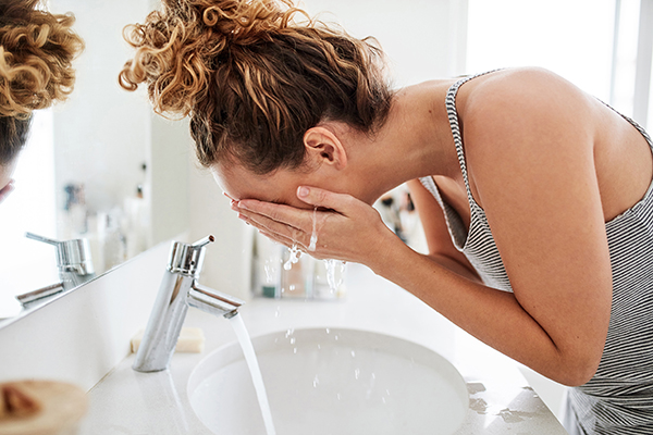 Shot of a young woman washing her face at the bathroom sink in the morning